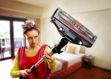 Femme au foyer avec l'aspirateur photos stock
