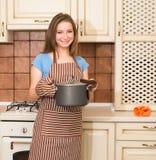 Femme au foyer avec la casserole et les gants d'isolation thermique Jeune femme 15 Photos libres de droits
