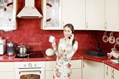 Femme au foyer avec la cuvette et le téléphone Photographie stock libre de droits