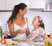 Femme au foyer avec la fille faisant cuire la tarte aux pommes Photographie stock