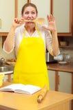Femme au foyer avec la poche dans la cuisine Image stock