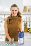 Femme au foyer avec le verre du broc de l'eau et de filtre d'eau photo stock
