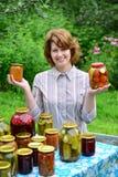 Femme au foyer avec les conserves au vinaigre et les confitures faites maison dans le jardin Photos stock