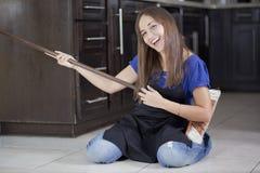 Femme au foyer ayant l'amusement avec un balai Photos stock