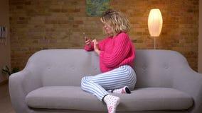 Femme au foyer blonde dans le chandail rose se reposant dans le profil sur le sofa surfant dans des sourires de smartphone à la c clips vidéos