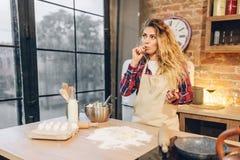 Femme au foyer contre la table avec de la farine, les oeufs et le lait photos stock
