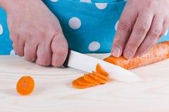 Femme au foyer coupant la carotte Photo stock