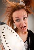 Femme au foyer criarde avec du fer de vapeur Photographie stock