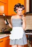 Femme au foyer d'une cinquantaine d'années dans la cuisine avec la bouteille et le verre de vin Photographie stock