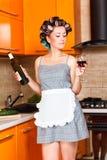 Femme au foyer d'une cinquantaine d'années dans la cuisine avec la bouteille et le verre de vin Photo libre de droits