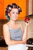 Femme au foyer d'une cinquantaine d'années de femme dans la cuisine avec la pomme Images libres de droits