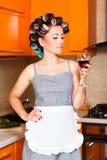 Femme au foyer d'une cinquantaine d'années féminine dans la cuisine avec le verre de vin Photos stock