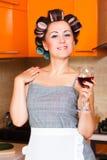 Femme au foyer d'une cinquantaine d'années féminine dans la cuisine avec le verre de vin Photo stock