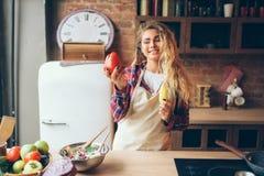 Femme au foyer dans le tablier tenant le poivre frais dans des mains images libres de droits