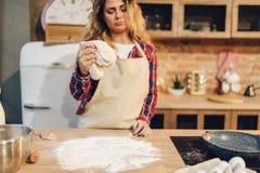 Femme au foyer dans un tablier faisant cuire la pâte dans la cuvette en métal image libre de droits