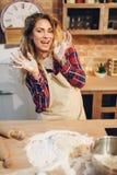 Femme au foyer dans un tablier faisant cuire la pâte dans la cuvette en métal images stock