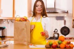 Femme au foyer de femme dans la cuisine avec beaucoup de fruits Images libres de droits