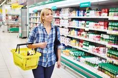 Femme au foyer de femmes avec des achats jaunes de panier dans le département de laiterie Photo libre de droits