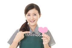 Femme au foyer de sourire avec le coeur rose Photographie stock