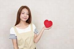 Femme au foyer de sourire avec un coeur rouge Photographie stock