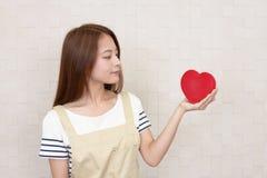 Femme au foyer de sourire avec un coeur rouge Image stock