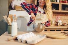 Femme au foyer de sourire dans le tablier faisant la pâte dans la cuvette photo stock