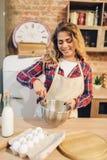 Femme au foyer de sourire dans le tablier faisant la pâte dans la cuvette image libre de droits