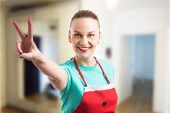Femme au foyer de sourire heureuse montrant à paix le geste vistory image stock
