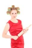 Femme au foyer drôle avec des bigoudis de rouleau-broche et de cheveu au-dessus de blanc Image stock