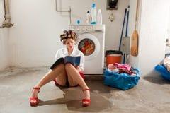 Femme au foyer ennuyée dans la blanchisserie Photographie stock libre de droits