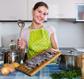 Femme au foyer essayant la nouvelle recette du sprattus dans la cuisine Photo stock