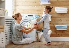 Femme au foyer et enfant heureux de mère de famille dans la blanchisserie avec le washin photos stock