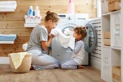 Femme au foyer et enfant heureux de mère de famille dans la blanchisserie avec le washin image libre de droits