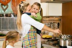 Femme au foyer et enfants ayant la tension Image stock