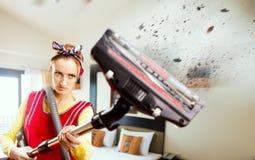 Femme au foyer fâchée dans le tablier avec l'aspirateur photo libre de droits