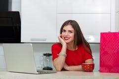 Femme au foyer fascinante faisant des emplettes en ligne Image libre de droits