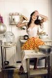 Femme au foyer folle de vraie femme sur la cuisine, mangeant Images libres de droits