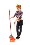 Femme au foyer gaie balayant le plancher Image libre de droits