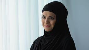 Femme au foyer heureuse dans le hijab souriant, culture islamique, bien-être femelle, traditions clips vidéos