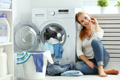 Femme au foyer heureuse de femme dans la buanderie près du machi de lavage photographie stock libre de droits