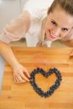 Femme au foyer heureuse faisant le coeur avec des myrtilles Photographie stock