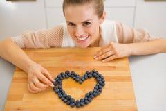 Femme au foyer heureuse faisant le coeur avec des myrtilles Images stock