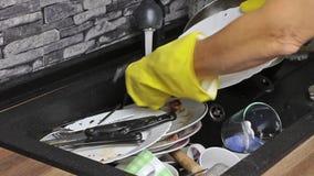 Femme au foyer lavant les plats sales dans l'eau clips vidéos