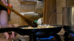 Femme au foyer mélangeant les légumes frais dans la poêle dans la cuisine préparant le dîner banque de vidéos