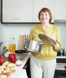 Femme au foyer mûre avec la casserole dans la cuisine à la maison Photographie stock libre de droits
