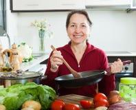 Femme au foyer mûre avec la poêle dans la cuisine à la maison Photographie stock
