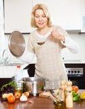 Femme au foyer mûre heureuse avec la poche faisant cuire la soupe dans la casserole dans la cuisine Image stock