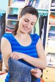 Femme au foyer mettant des vêtements sur l'espace procurable photographie stock