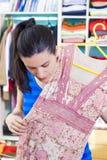 Femme au foyer mettant des vêtements sur l'espace procurable Photo libre de droits