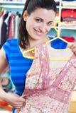 Femme au foyer mettant des vêtements sur l'espace procurable photos stock